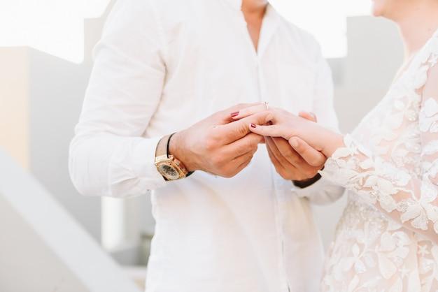 Jovem casal usando vestido de noiva branco e camisa, trocando alianças em sua cerimônia de casamento de sonho