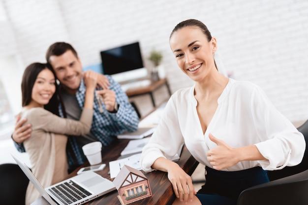 Jovem casal vende casa na agência imobiliária.