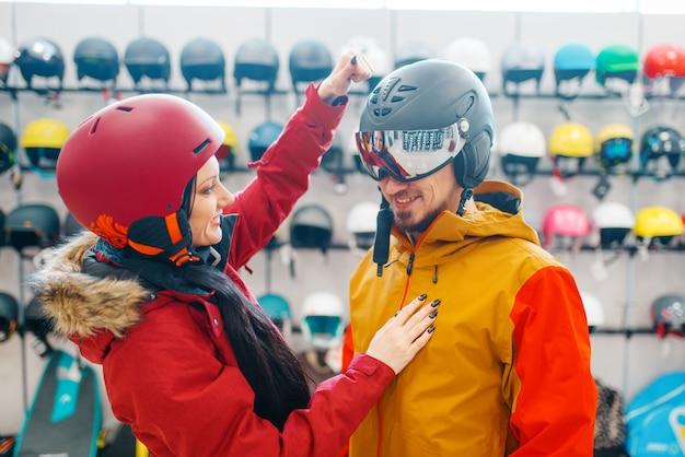 Jovem casal verifica a resistência do capacete de esqui ou snowboard, loja de esportes.