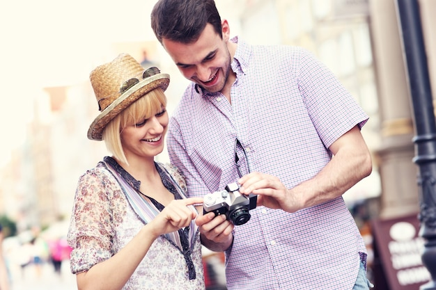 Jovem casal verificando fotos em sua câmera enquanto visita gdansk, na polônia