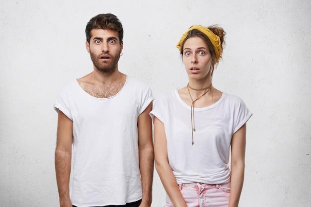 Jovem casal vestido casualmente, posando para a parede do estúdio
