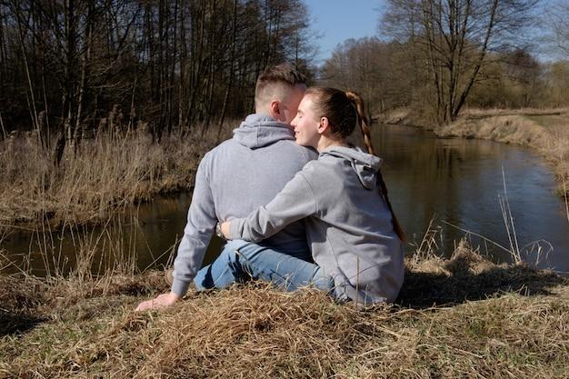 Jovem casal vestido com jeans e hoodies cinza, sentado na margem do rio da floresta