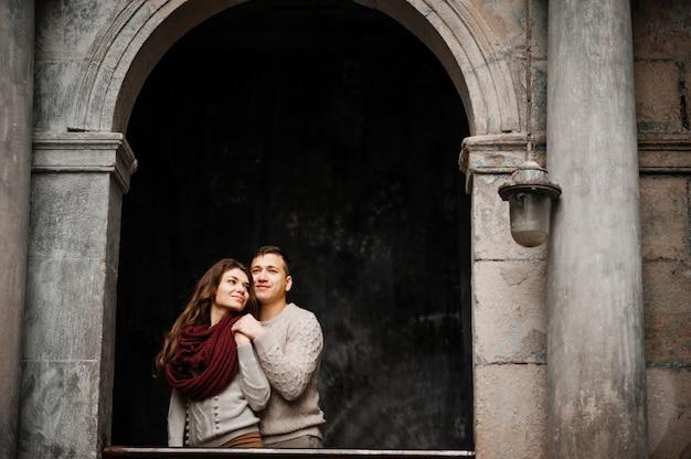 Jovem casal vestindo blusas quentes amarradas, abraçando no amor no velho quintal com arco e colunas na cidade.