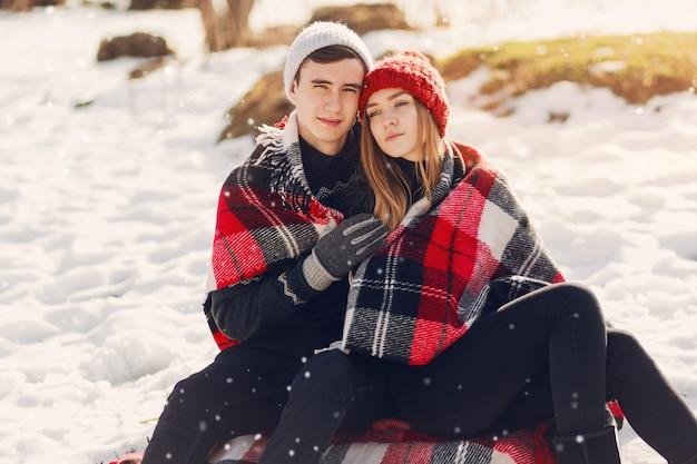 Jovem casal vestindo cobertor em um campo nevado