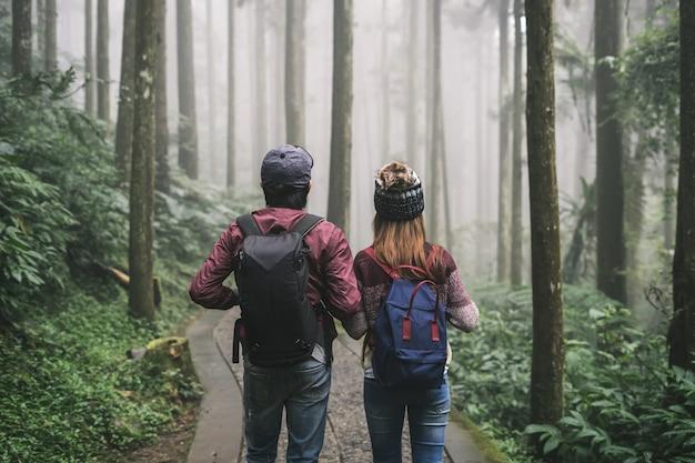 Jovem casal viajante com mochila segurando a mão juntos
