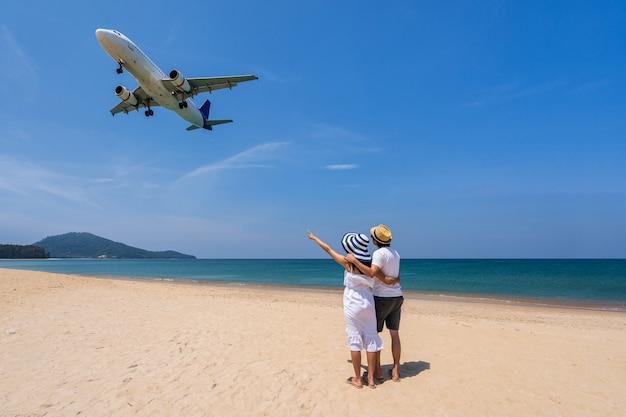Jovem casal viajante olhando para o avião enquanto pousa em uma praia tropical, conceito de férias de verão