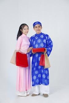 Jovem casal vietnamita positivo em um costume tradicional para o ano novo lunar conhecido como feriado do tet