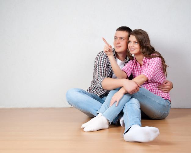 Jovem casal visualizando a decoração de sua nova casa sentado no chão de madeira nua, apontando para fora e discutindo a colocação de móveis