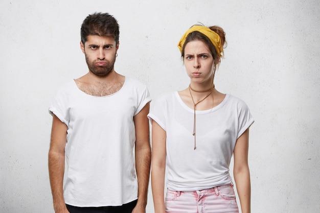 Jovem casal zangado com expressões amuadas, assoando o rosto em desespero, tendo relacionamentos ruins