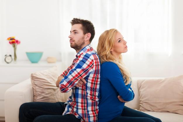 Jovem casal zangado sentado de costas para a casa