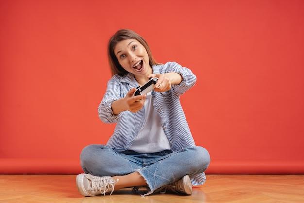 Jovem casual animada jogando videogame se divertindo na parede vermelha