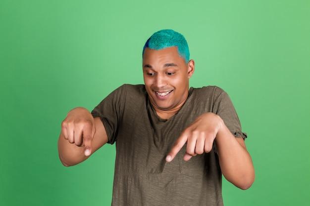 Jovem casual com parede verde, cabelo azul apontando o dedo para baixo