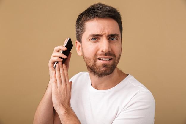 Jovem casual confuso segurando o celular isolado
