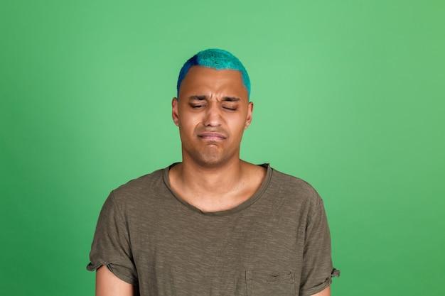 Jovem casual na parede verde cabelo azul infeliz triste chorando