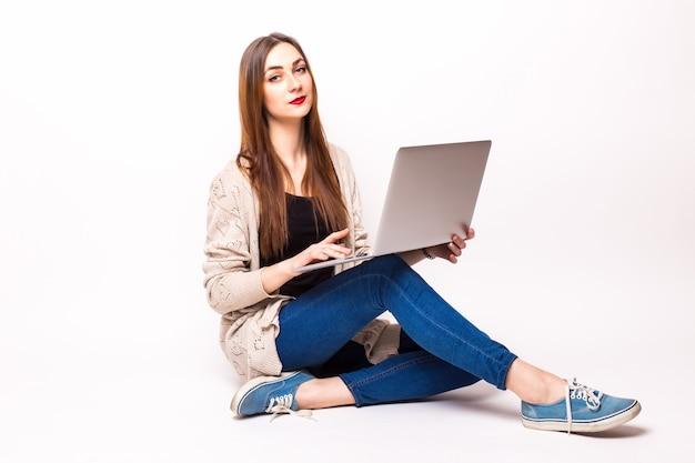 Jovem casual sentada sorrindo segurando um laptop