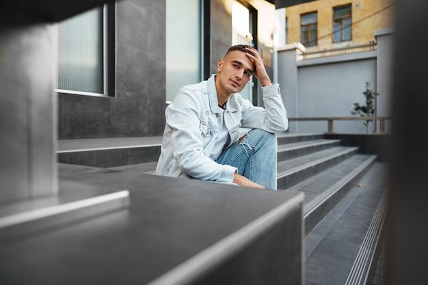 Jovem casual sentado na escada sozinho na rua