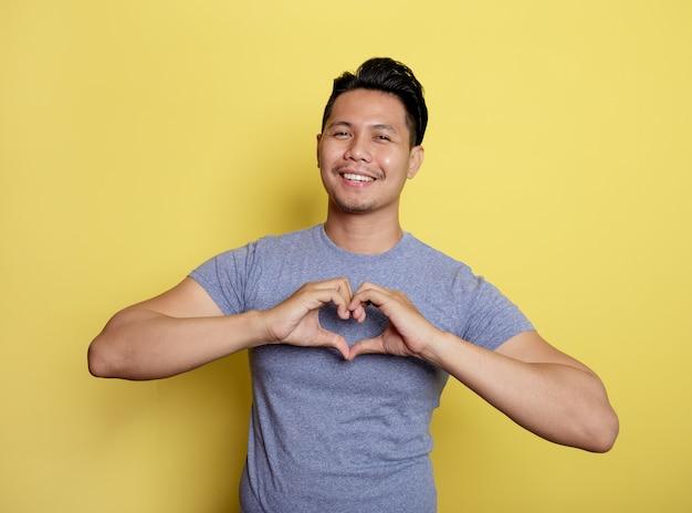 Jovem casual sorriso expressão sinal de amor com as mãos isoladas em um fundo de cor amarela
