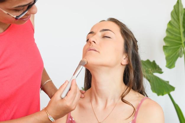 Jovem caucasiana a maquiar-se para um casamento