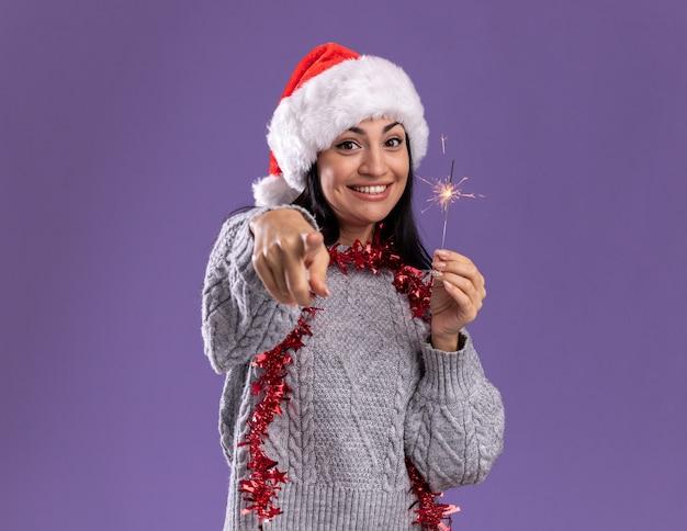 Jovem caucasiana alegre com chapéu de natal e guirlanda de ouropel no pescoço segurando um diamante de feriado olhando e apontando para a câmera isolada no fundo roxo