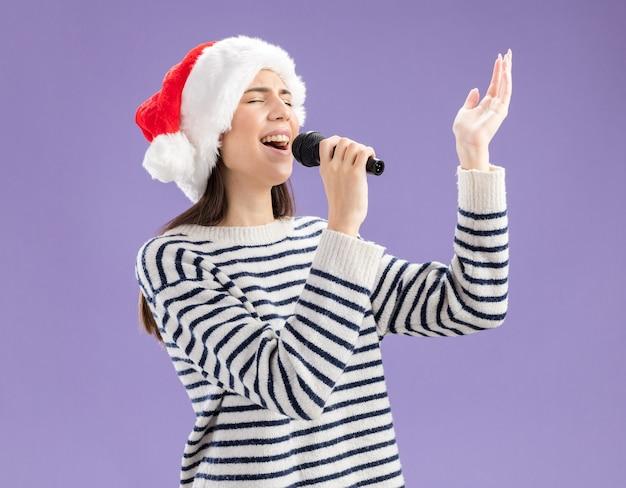 Jovem caucasiana alegre com chapéu de papai noel segurando microfone e fingindo cantar