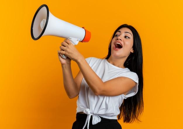 Jovem caucasiana alegre segurando um alto-falante olhando para o lado