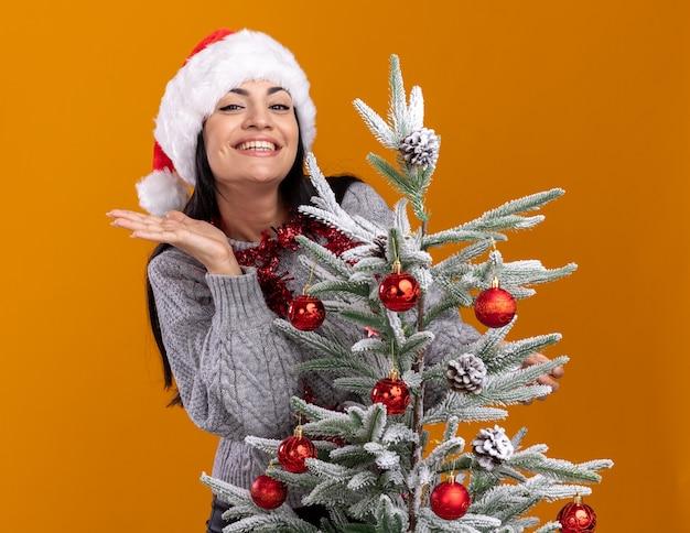 Jovem caucasiana alegre usando chapéu de natal e guirlanda de ouropel em volta do pescoço em pé atrás de uma árvore de natal decorada, mostrando a mão vazia isolada na parede laranja