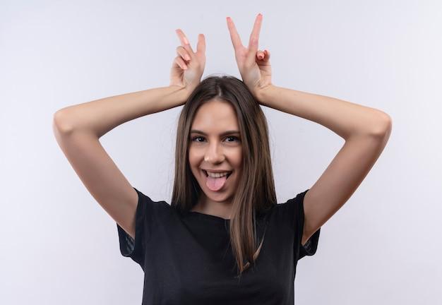 Jovem caucasiana alegre vestindo uma camiseta preta mostrando gesto de língua e orelhas de coelho na parede branca isolada
