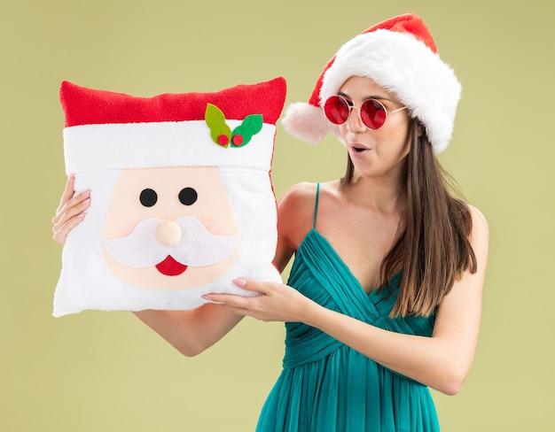 Jovem caucasiana animada com óculos de sol e chapéu de papai noel segurando uma almofada de papai noel isolada na parede verde oliva com espaço de cópia