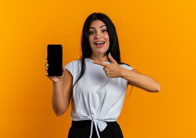 Jovem caucasiana animada segurando e apontando para o telefone