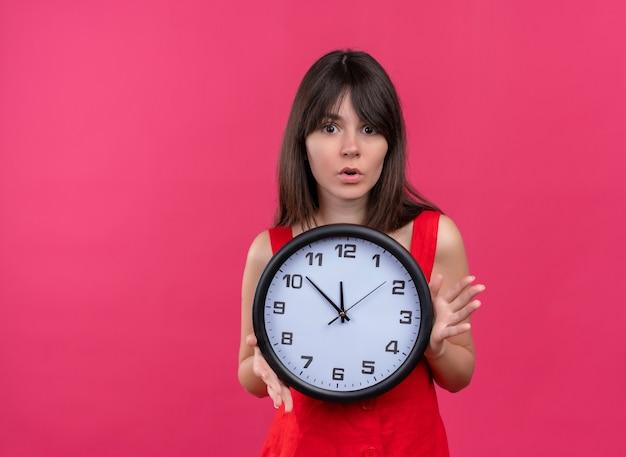 Jovem caucasiana ansiosa segurando o relógio com as duas mãos e olhando para a câmera em um fundo rosa isolado com espaço de cópia