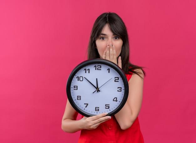 Jovem caucasiana ansiosa segurando o relógio e segurando a boca, olhando para a câmera em fundo rosa isolado
