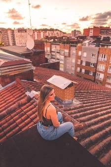 Jovem caucasiana, apreciando o pôr do sol com uma vista do telhado sobre donostia-san sebastian, país basco.
