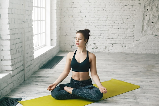 Jovem caucasiana atraente fazendo exercícios em casa, fazendo exercícios de ioga em um tapete verde, sentada em posição de lótus com as pernas dobradas e os olhos fechados, meditando, respirando profundamente, relaxando o corpo e a mente