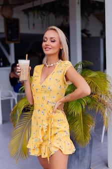 Jovem caucasiana, calma, bonita, feliz, com maquiagem brilhante para a noite, usando um vestido amarelo de verão e um colar de conchas do mar