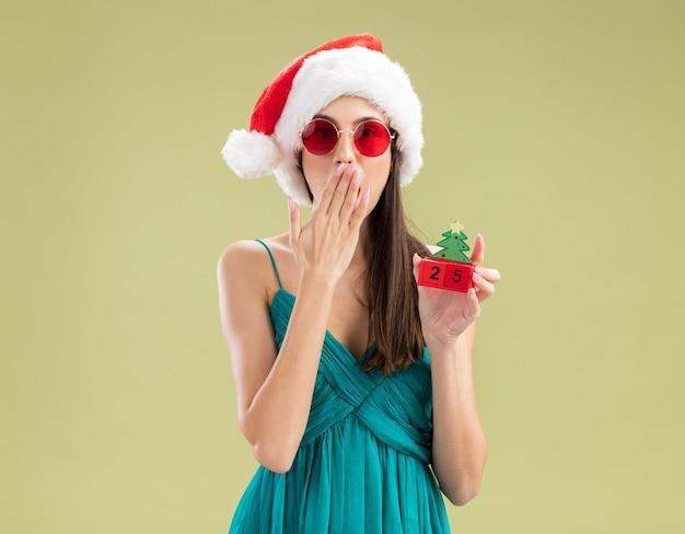 Jovem caucasiana chocada com óculos de sol e chapéu de papai noel coloca a mão na boca e segura o enfeite de árvore de natal