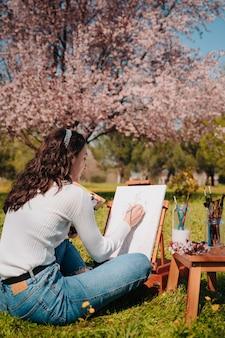Jovem caucasiana com cabelos ondulados pintando uma tela com tintas rosa pastel em pé na natureza de um parque, em frente a uma amendoeira gigante rosa.