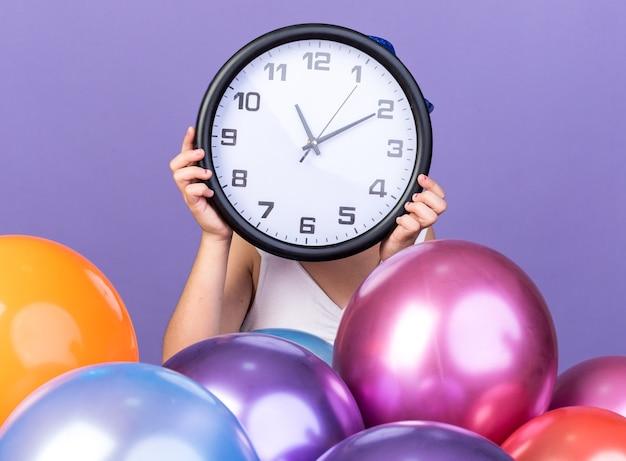 Jovem caucasiana com chapéu de festa azul segurando o relógio na frente do rosto em pé com balões de hélio isolados na parede roxa com espaço de cópia
