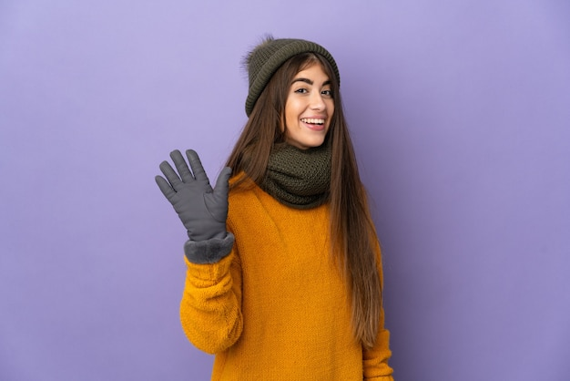 Jovem caucasiana com chapéu de inverno isolada em fundo roxo saudando com a mão com expressão feliz