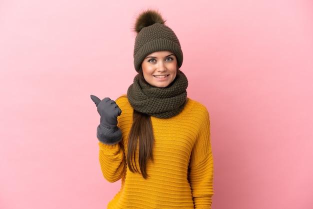Jovem caucasiana com chapéu de inverno isolada em um fundo rosa apontando para o lado para apresentar um produto