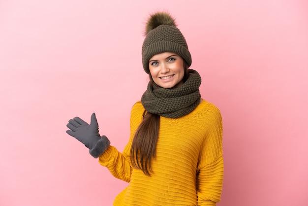 Jovem caucasiana com chapéu de inverno isolada em um fundo rosa, estendendo as mãos para o lado para convidar para vir