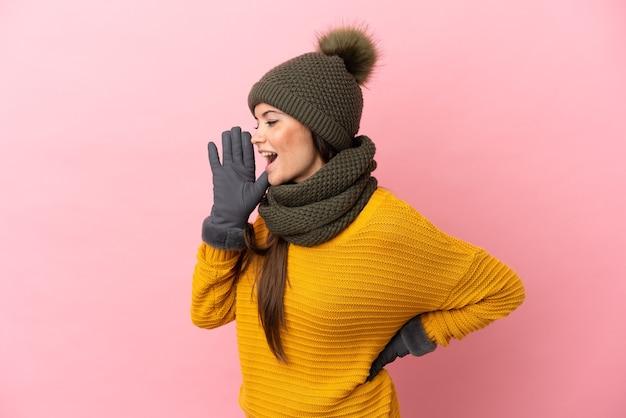 Jovem caucasiana com chapéu de inverno isolada em um fundo rosa gritando com a boca bem aberta para o lado