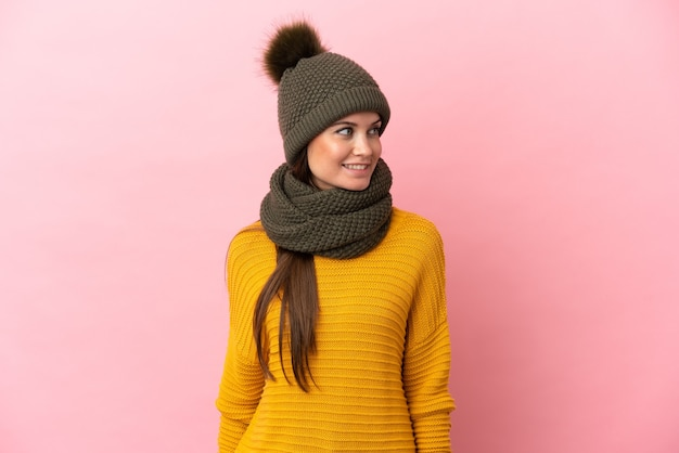 Jovem caucasiana com chapéu de inverno isolada em um fundo rosa olhando para o lado e sorrindo