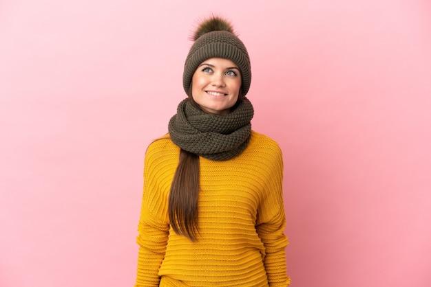 Jovem caucasiana com chapéu de inverno isolada em um fundo rosa pensando em uma ideia enquanto olha para cima
