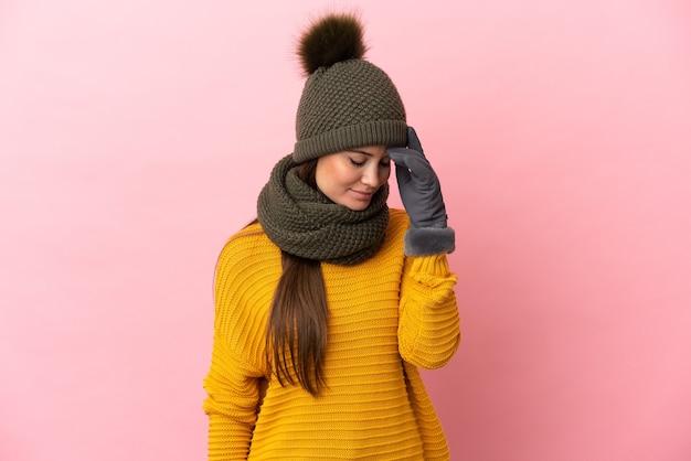 Jovem caucasiana com chapéu de inverno isolada em um fundo rosa rindo