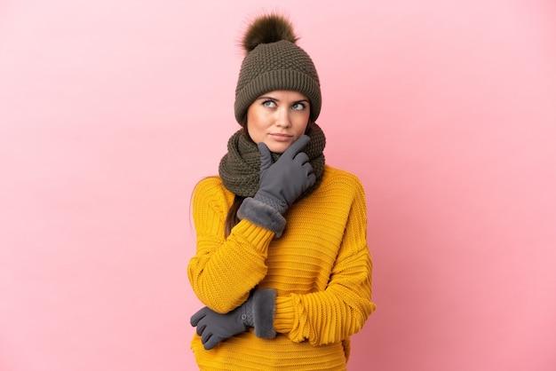 Jovem caucasiana com chapéu de inverno isolada em um fundo rosa tendo dúvidas