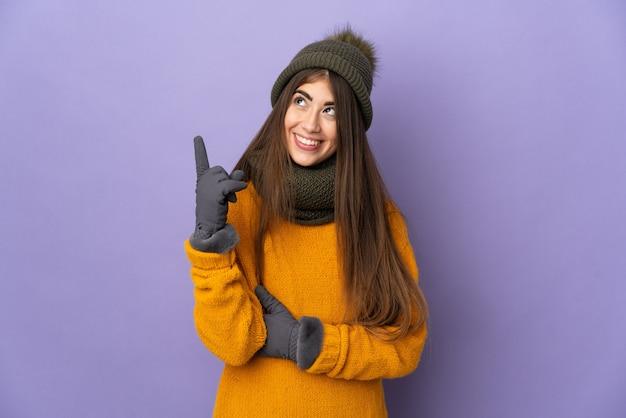 Jovem caucasiana com chapéu de inverno isolada em um fundo roxo apontando para uma ótima ideia