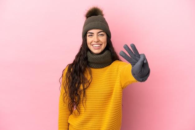 Jovem caucasiana com chapéu de inverno isolada em um fundo roxo feliz e contando três com os dedos