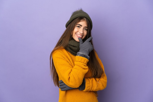 Jovem caucasiana com chapéu de inverno isolada em um fundo roxo feliz e sorridente