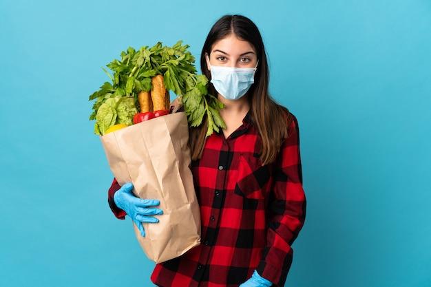 Jovem caucasiana com vegetais e máscara isolada em azul com expressão facial surpresa e chocada