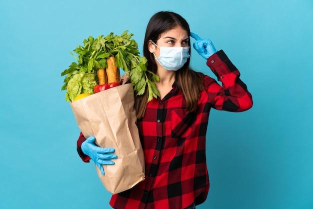 Jovem caucasiana com vegetais e máscara isolada na parede azul com dúvidas e com expressão facial confusa